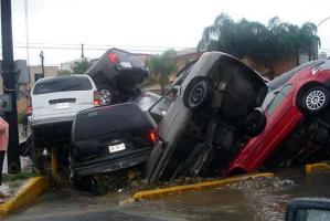 Algunos automóviles que fueron arrastrados por la corriente, cerca del Puente Solidaridad y Paseo de las Americas